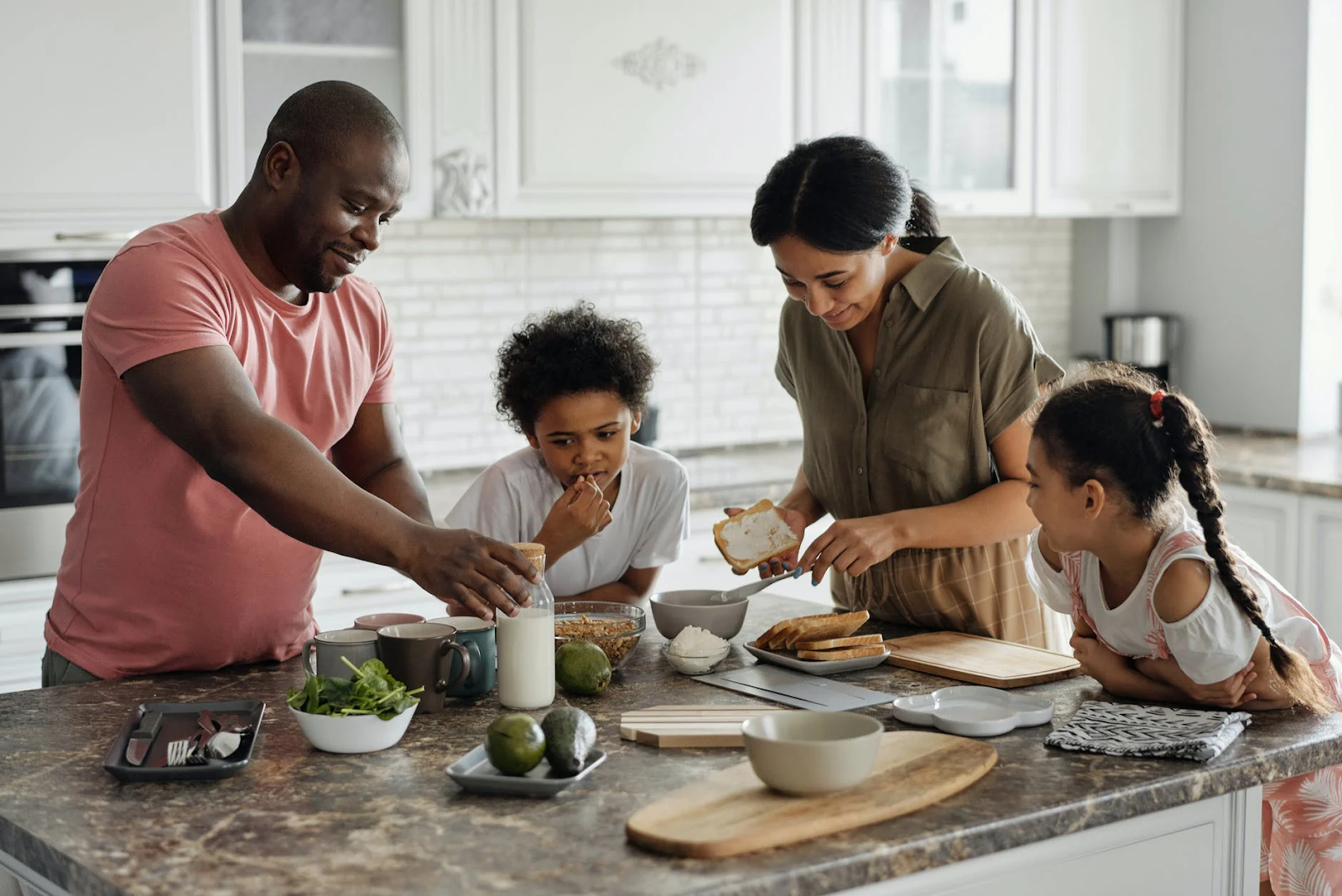 image shows two parents and two children cooking together