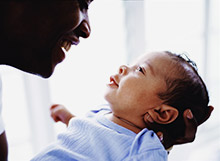 Father and newborn smiling at each other.