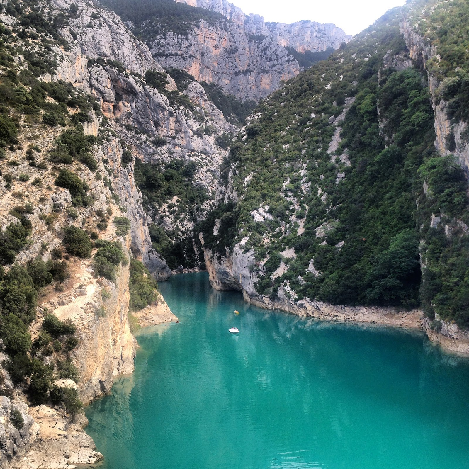 verdon gorge national park, turquoise calm lake surrounded by large limestone cliffs covered in green bushes. No tourists on this sunny day in french riviera, cote d'azur.
