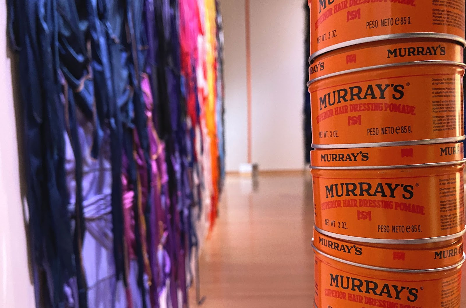 Image: On the right, a detail of a totem sculpture made of stacked Murray's Superior Hair Dressing Pomade cans. The cans are orange, with black and red text. On the left, an out-of-focus view of a colorful durag painting, and another totem sculpture. Photo by Jessica Hammie.