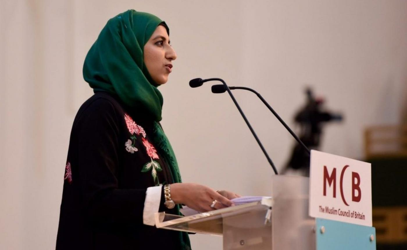 A person in a green head scarf speaking into a microphone  Description automatically generated with low confidence