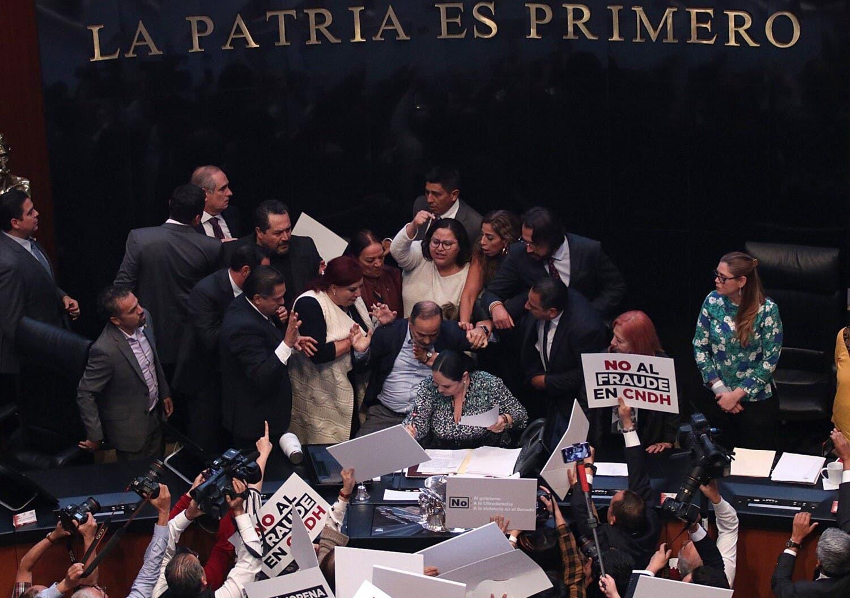 Senadores se enfrentan a golpes ayer durante la toma de Rosario Piedra como presidenta de la CNDH (EFE)