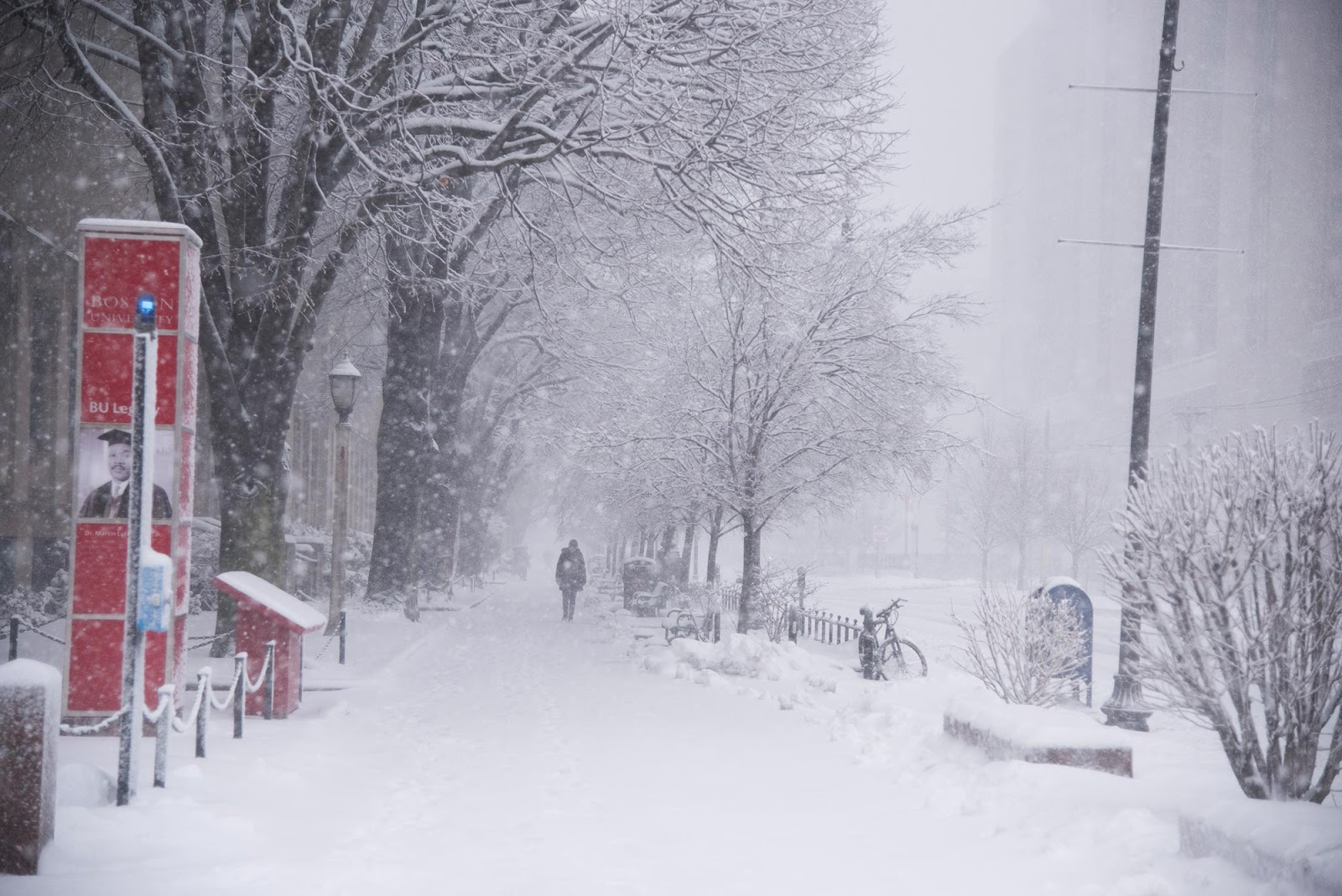 Photo taken during a Nor'Easter in 2018; the sidewalk is covered with snow as figure in jacket walks down. Snow falling blurs the image.