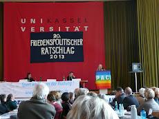 Bühne, Podium, Redner am Pult. Dahinter großes Transparent: »Uni Kassel,  20. Friedensratschlag 2013«.