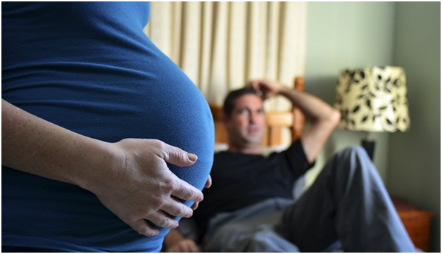 women holding her pregnant belly because of Frequent Urination in pregnancy