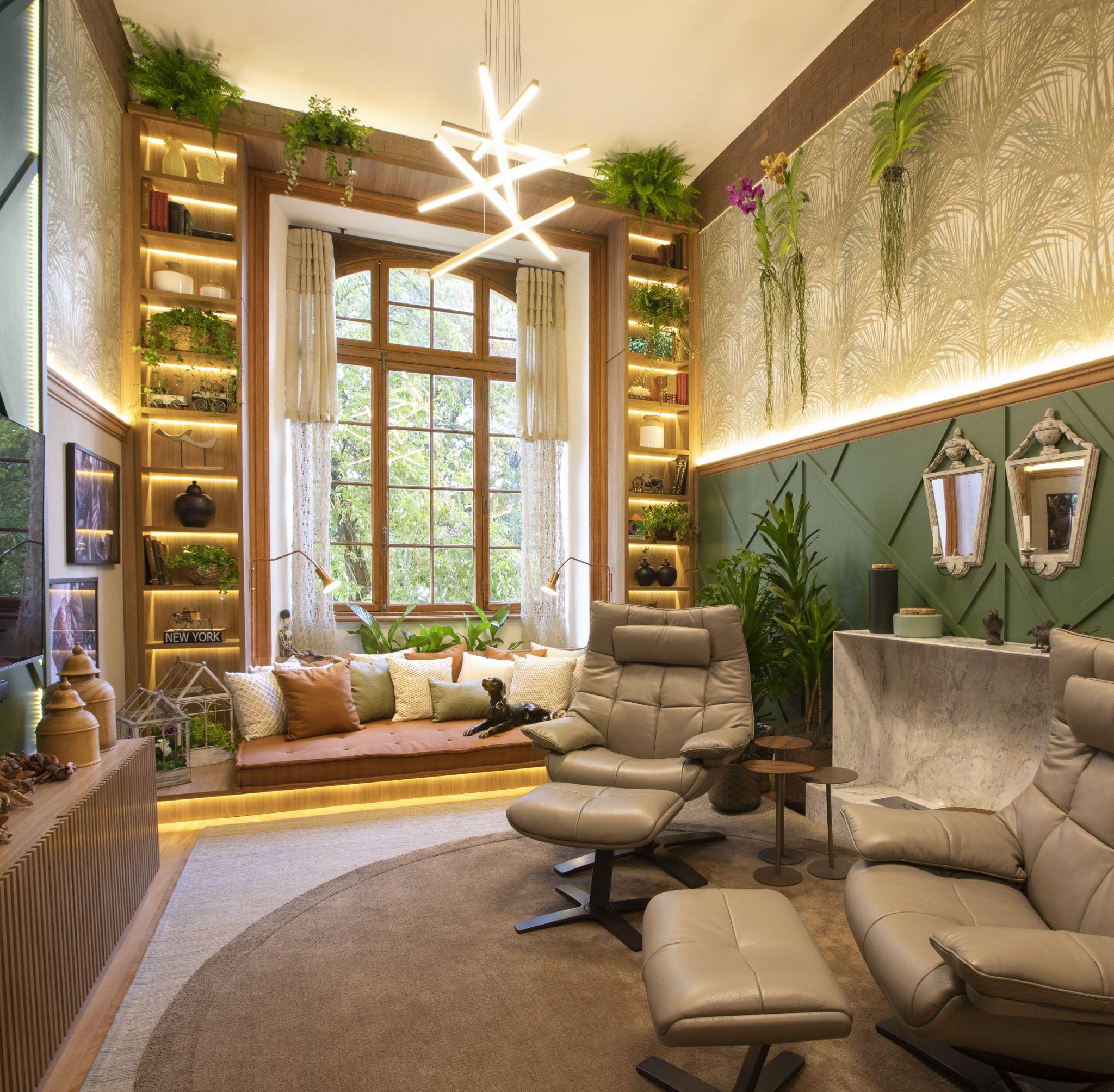 Sala com poltronas cinza, sofá no canto da janela com almofadas coloridas, meia parede verde de fundo e outra metade com papel de parede biofilia, janela grande de madeira com nichos nas laterais