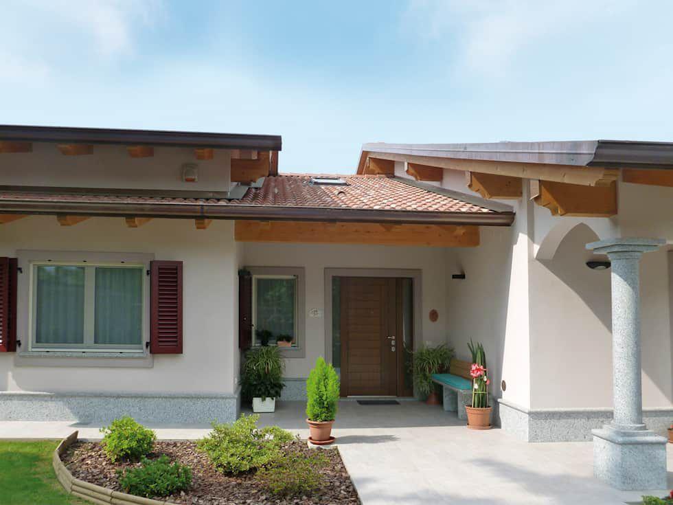 Vista frontal externa de uma residência, com uma janela ampla, uma janela pequena, e uma porta ampla. É possível identificar, também, um pilar e parte do jardim. Imagem para ilustrar a reforma de casas.