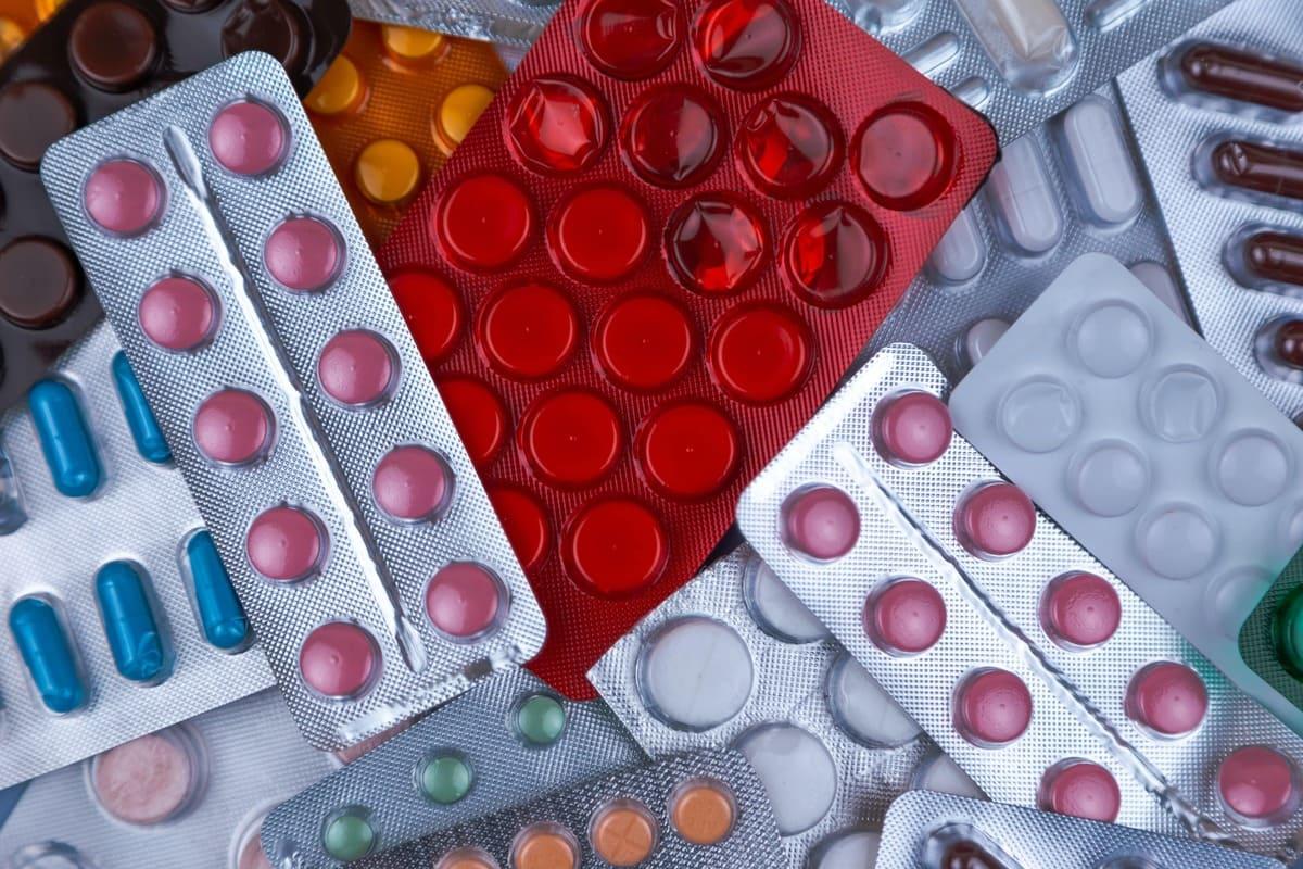 Diverse pastiglie di medicinali di diversi colori sparsi su una superficie