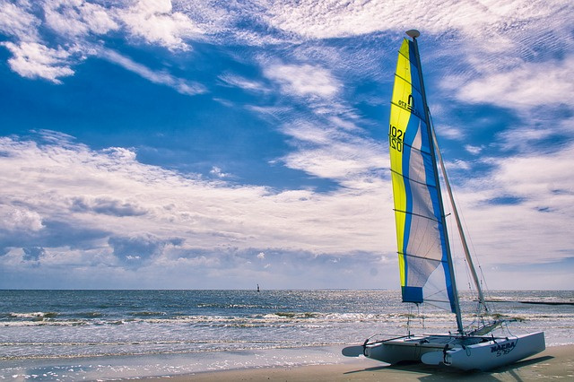 Siting on a beach, a small catamaran sail is set against the wind swept clouds and blue sky.