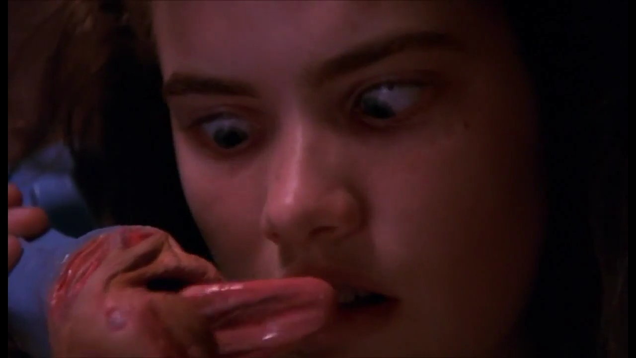 Screencap from the movie Nightmare on Elm Street. Nancy, a young dark haired white woman, is looking down at her phone in confused terror because the receiver now has lips and a tongue wagging at her.