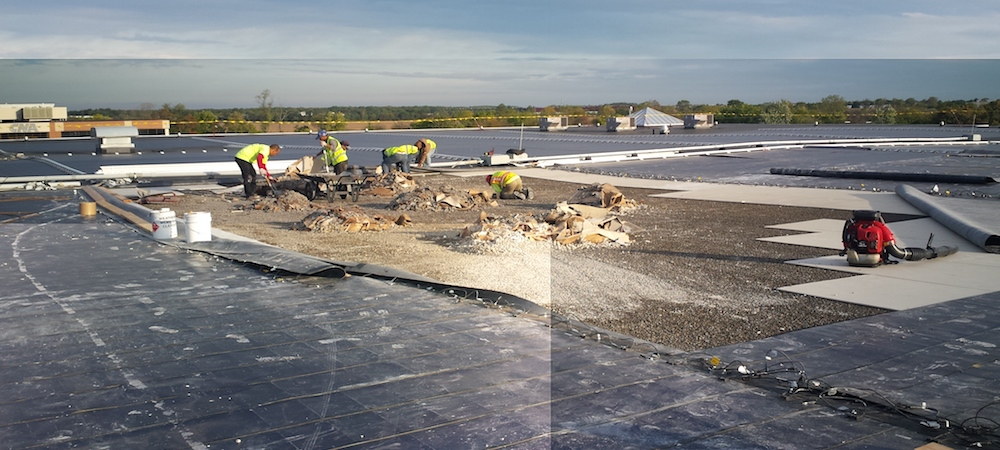 A team of roofers perform a commercial roof repair.