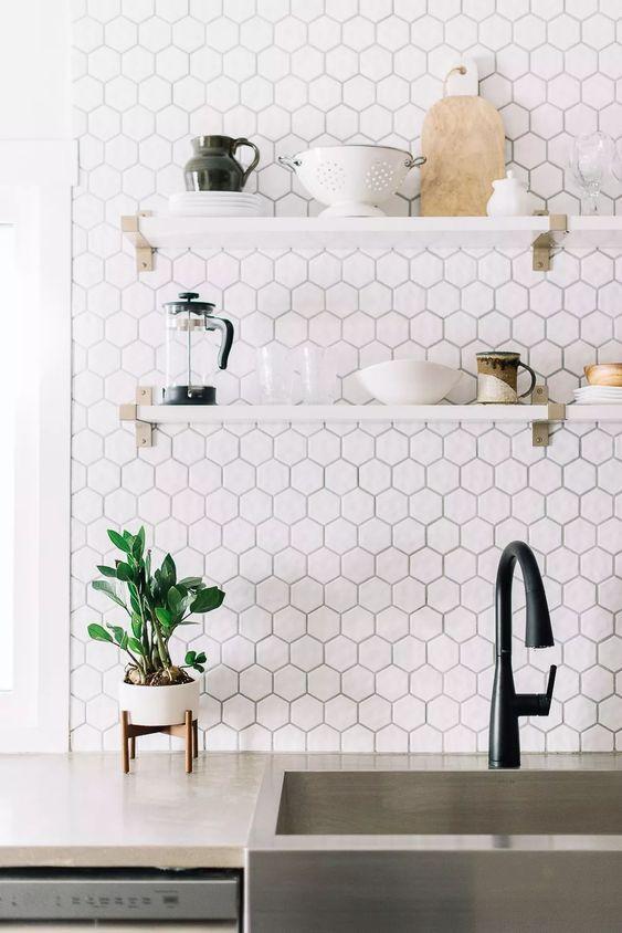 Cozinha com parede da pia com revestimento hexagonal em formato pequeno branco, prateleiras branca com utensílios de cozinha e torneira preta.