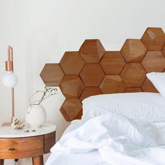 Quarto com cama de casal com cabeceira de revestimento hexagonal amadeirado, parede fundo branca, mesinha de canto amadeirado com bancada branca e abajur.