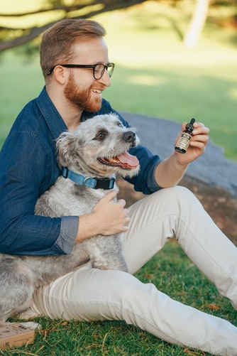 Man  smiling and holding his dog and CBD Oil