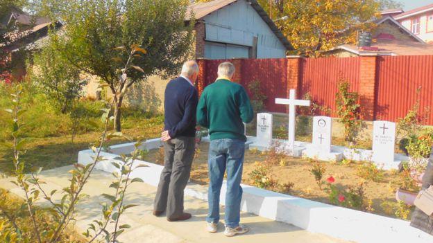 Братья Джеймс и Даг Дайкс у могилы своих родителей.