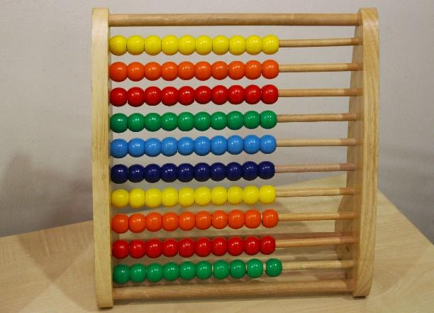A picture containing object, abacus, indoor, table  Description generated with very high confidence