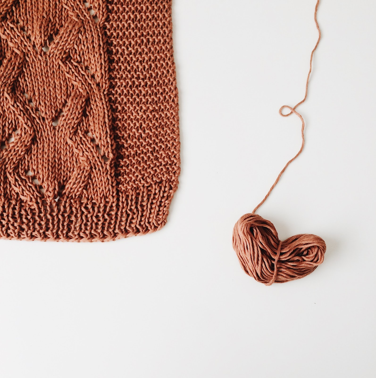 yarn in a heart shape next to a knitted sweater