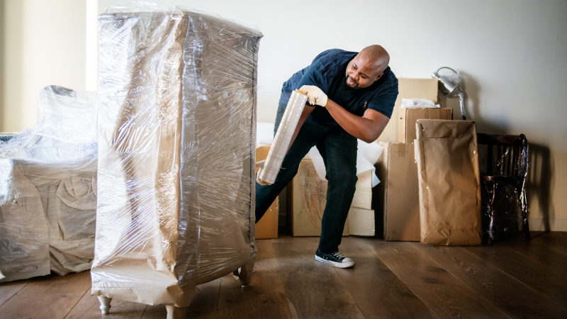 A man wrapping furniture before moving it into a storage container