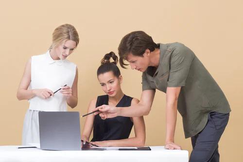 três pessoas de frente a um computador - Code Review