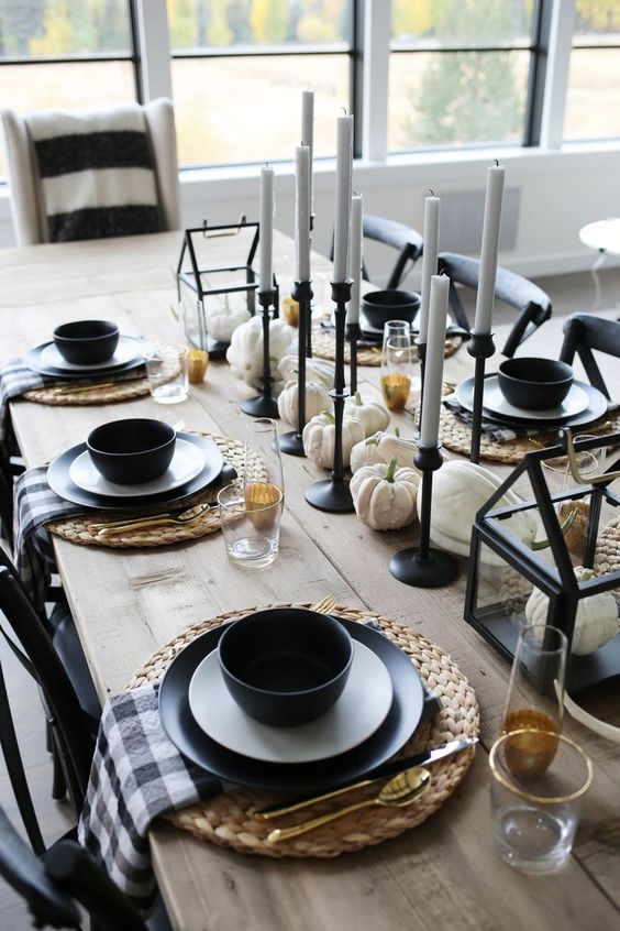 Black and white dining table setup with candles and white pumpkins and gordes.