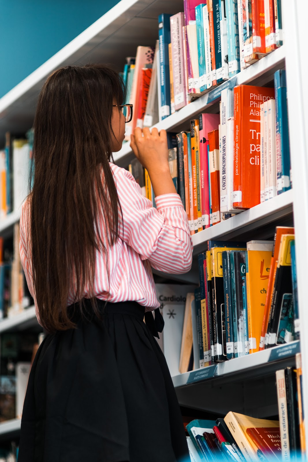 A young girl faces a shelf full of books at the library and appears to be choosing one.