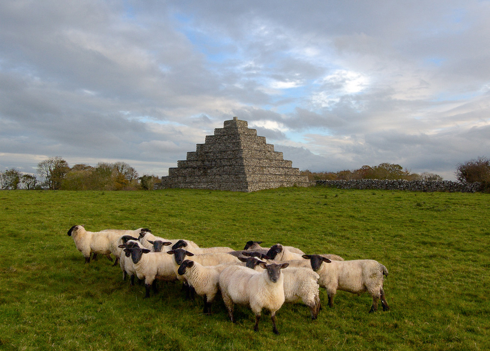 A photograph of a group of sheep in the foreground and a pyramid in the background with trees in the far background below a cloudy sky.