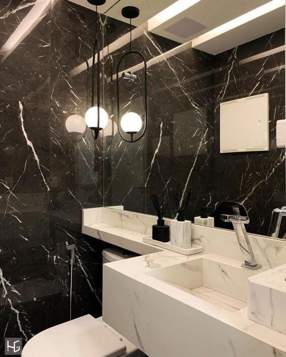 Banheiro com pia revestida de porcelanato marmorizado branco, parede revestida de porcelanato marmorizado preto