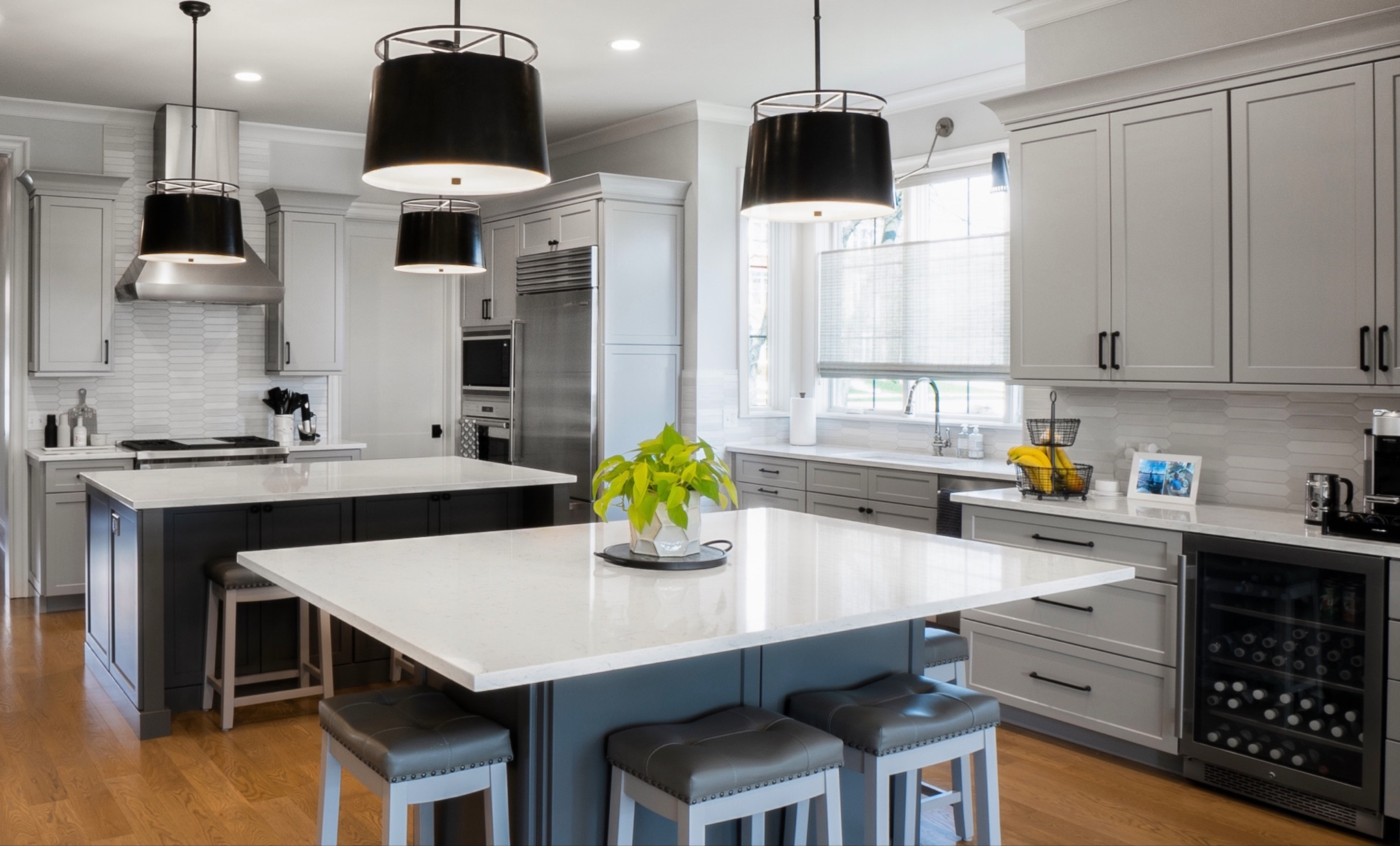 Kitchen featuring white cabinetry, stainless steel appliances, double islands with contrasting gray cabinetry and large, black drum pendant lights.