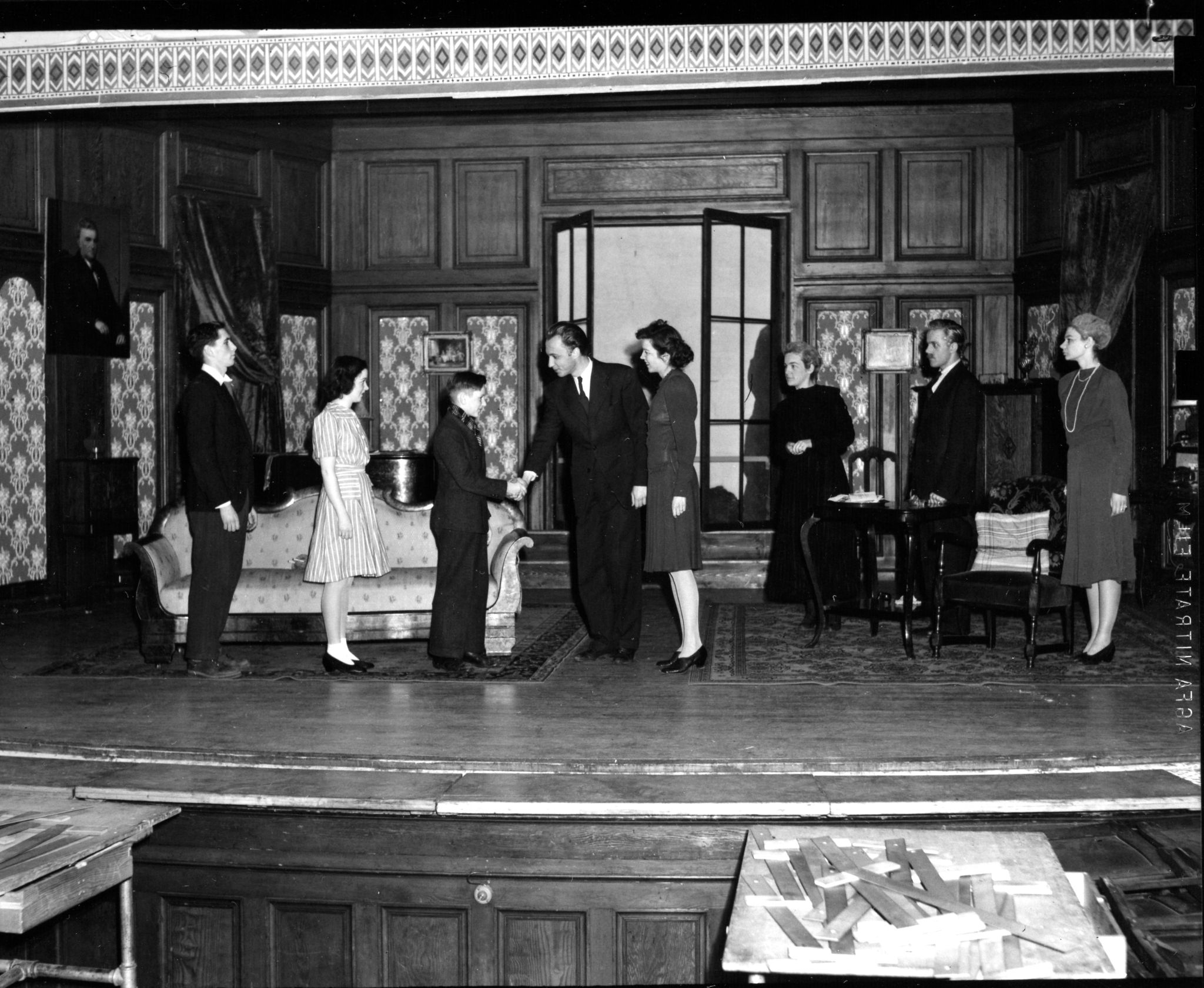 Black and white photo of a play. On stage, a young Caucasian man and woman shake hands with a Caucasian boy in a suit and tie. Several other people look on. The stage is decorated with wood paneling and formal furniture.