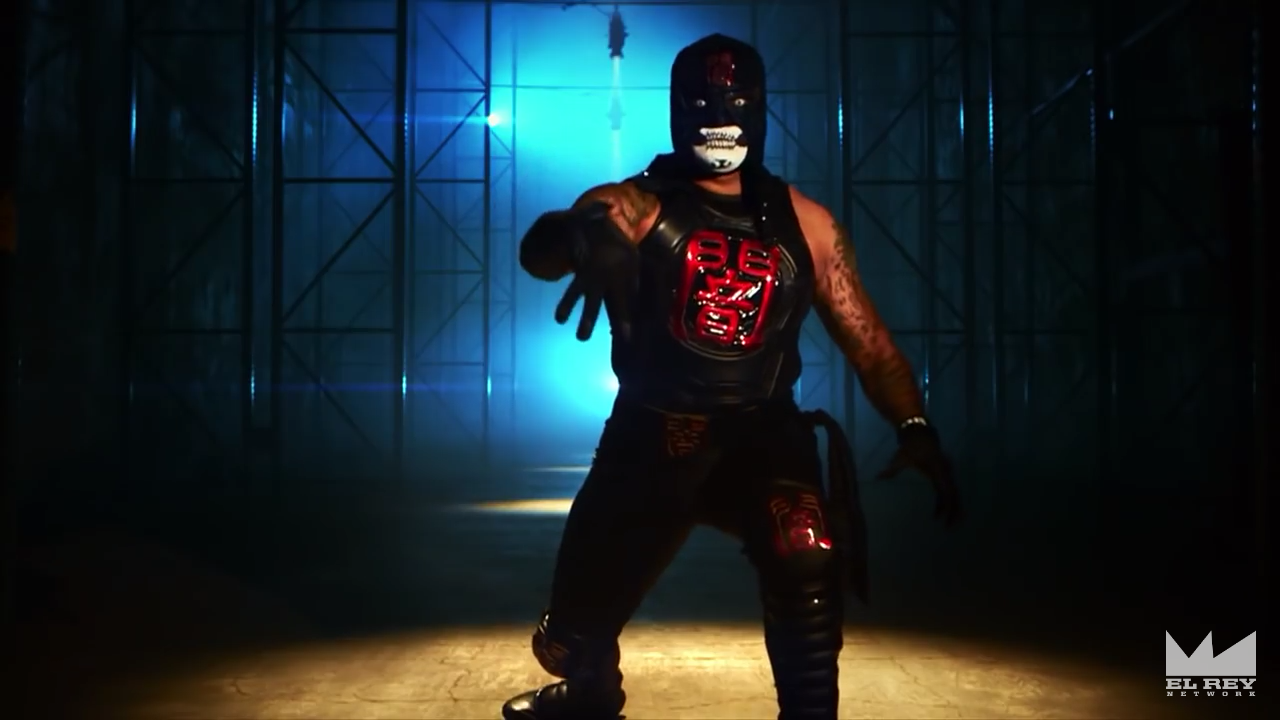 Image is Pentagon Dark, a man wearing a black and red ninja-inspired outfit and a mask with the lower half of his face painted white. He is striking a menacing pose with 4 of his fingers pointing downward, suggesting the letter M.