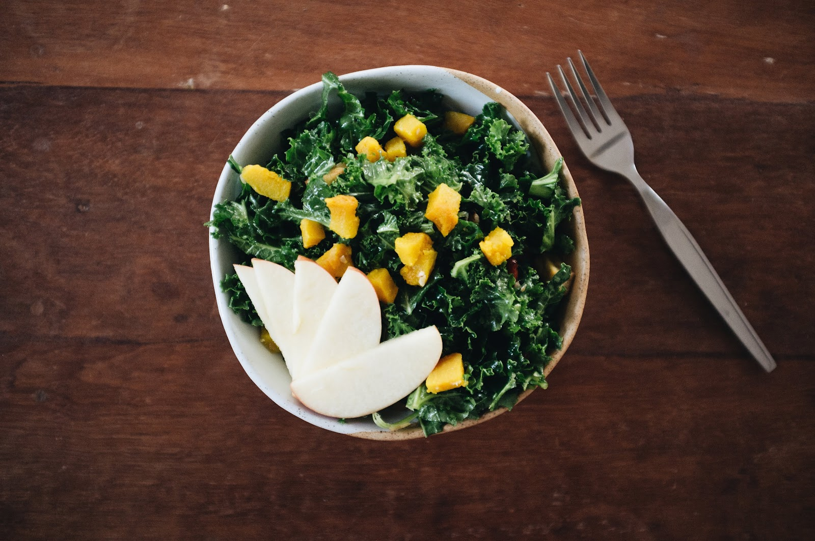 Kale and fruit salad in a bowl on a table with a fork.