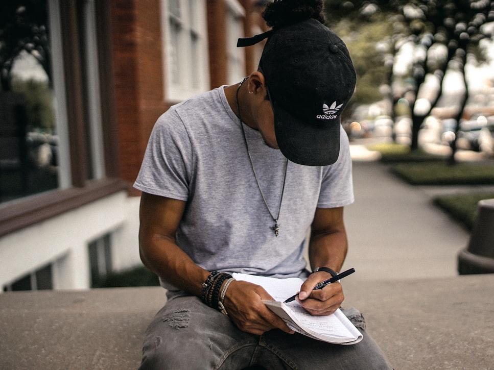 Menino sentando escrevendo em um caderno