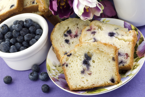 PIcture: a small bowl of fresh blueberries next to a loaf of blueberry infused sweet bread.