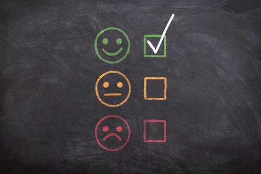 blackboard with a happy face, neutral face, and sad face
