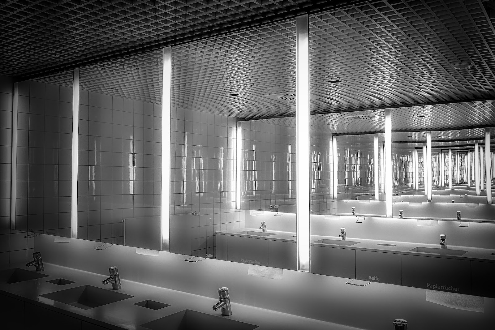Two bathroom mirrors make what appears to be a never ending reflection of each other, similar to the effects of an infinity mirror.