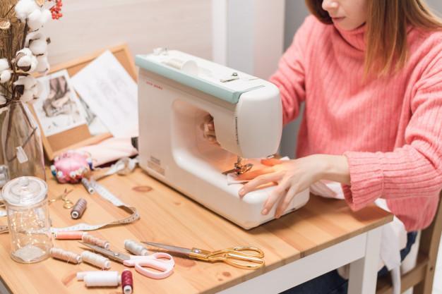 Швея работает на швейной машинке. женщина шьет и держит розовую ткань | Премиум Фото