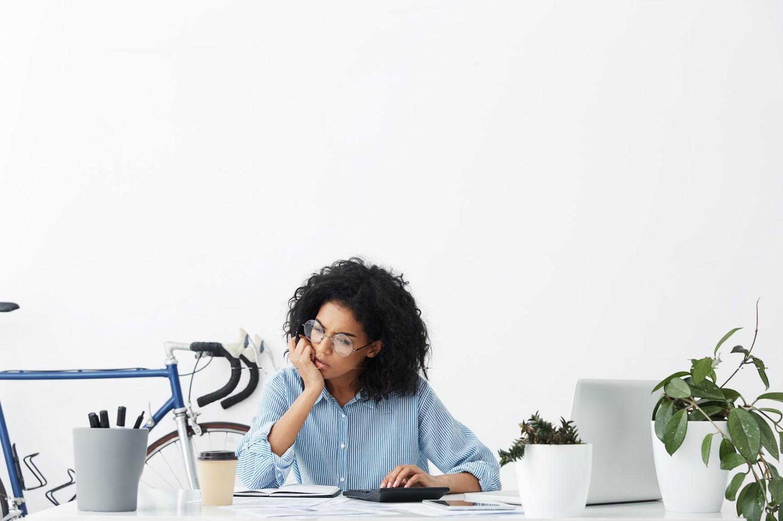Imagem de uma mulher negra em uma mesa, com um café em sua frente. Uma de suas mãos está em seu queixo e sua feição está preocupada com o balancete contábil. A outra mão está em cima de um calculadora. Na mesa, identificamos um caderno, café, canetas e vasos. A imagem possui fundo branco e todos os elementos brancos, exceto por uma bicicleta azul ao fundo e a camisa azul da mulher.