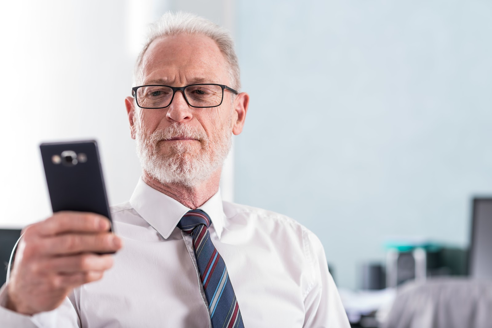 older business man looking at phone