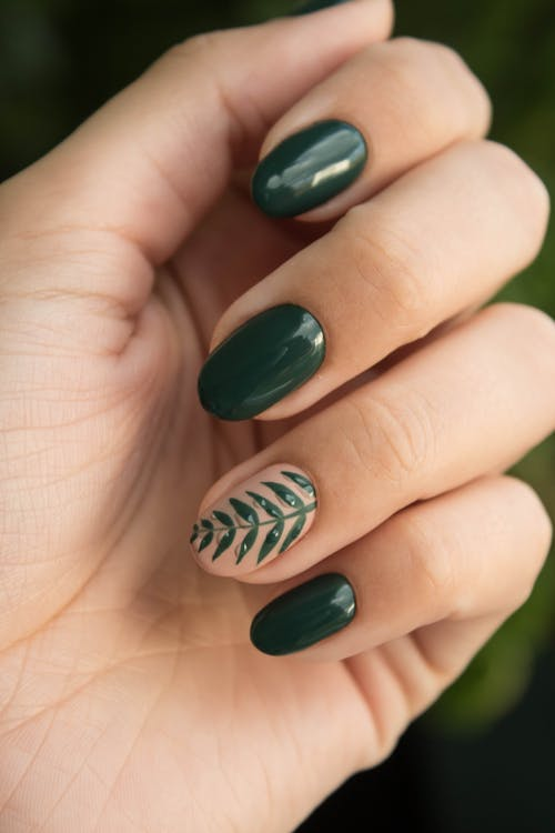 Green nails with 1 accent nail featuring a botanical plant on the ring finger