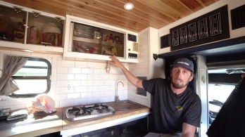 man showing kitchen in ambulance tiny home