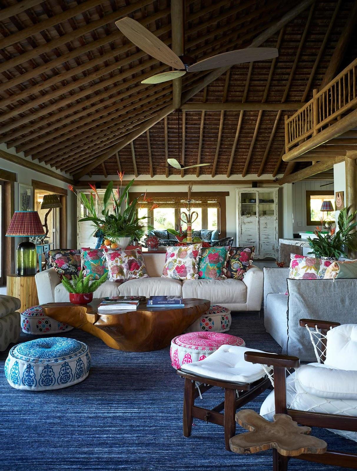 Sala com tapete azul, moveis de madeira e almofadas florais Sig Bergamin