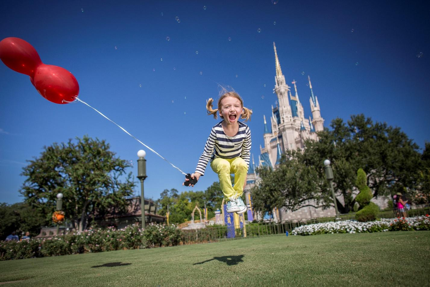 Young blonde girl jumping for joy holding a red mickey mouse balloon in front of the Walt Disney World castle