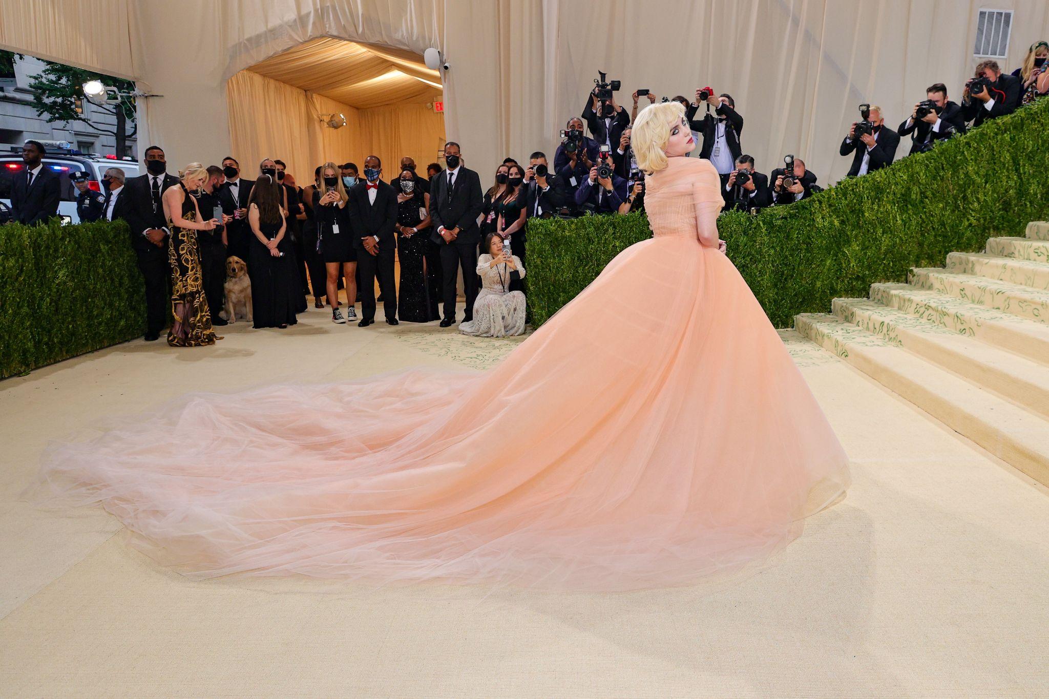 Mulher branca tem cabelos brancos curtos, com vestido cor bege claro com com cauda arrastando no chão. Foto: Getty Images. Post Looks icônicos do VMA e Met Gala 2021.
