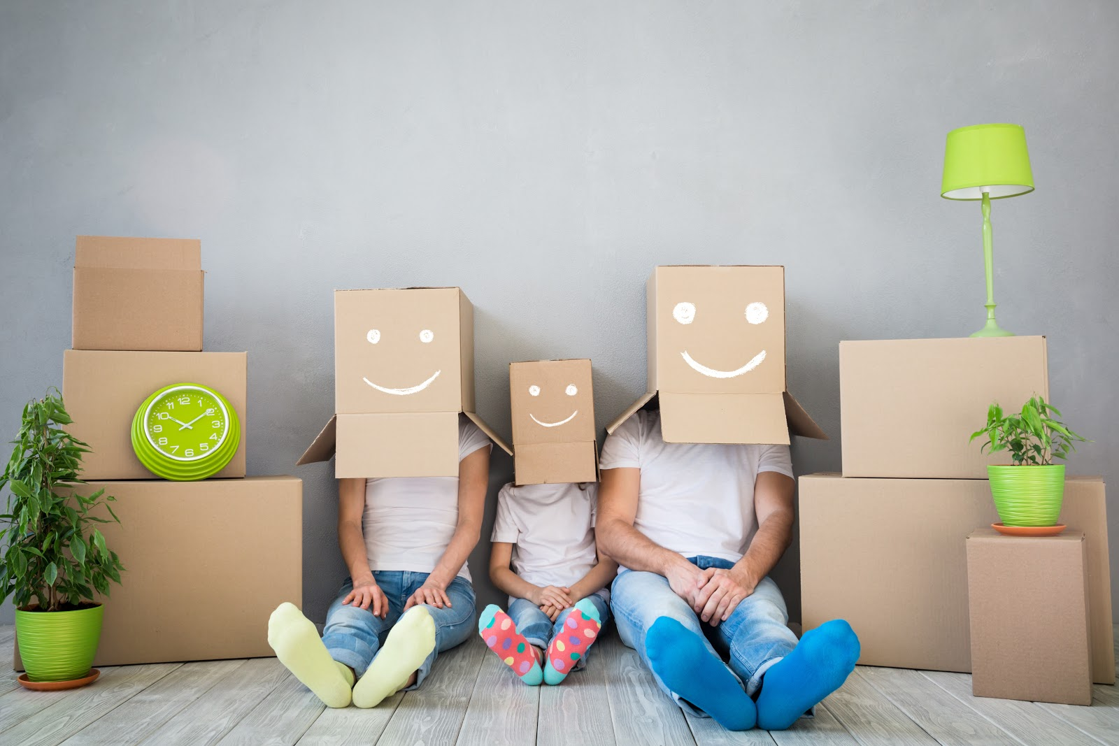 A family with moving boxes painted with smiley faces on their heads