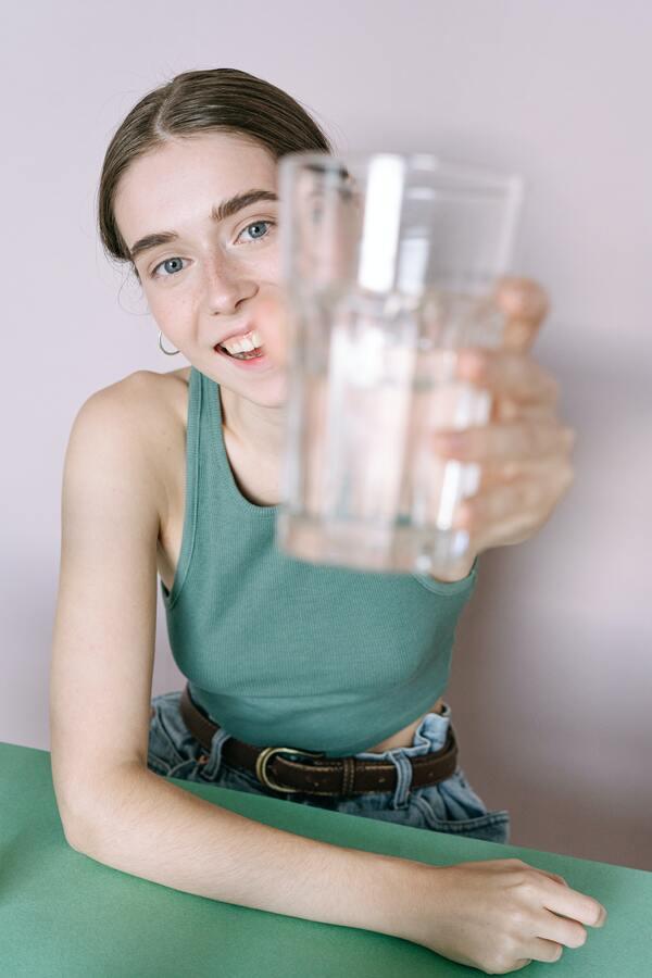 foto de uma mulher segurando um copo de vidro