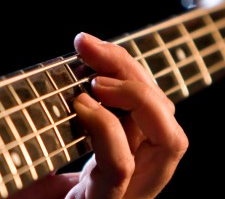 Fingers on a bass guitar neck