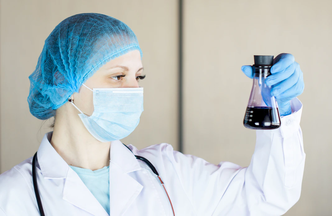 nurse in a blue knit cap and white lab coat holding a beaker with a purple liquid inside of it