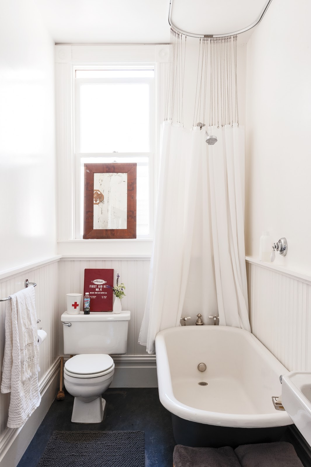 In her wee bath, clothing designer Dagmar Daley ditched her curtains, used all white to maximize the sense of light and air, and she used vertical elements, wainscoting and a shower curtain, to emphasize the height of the room.Photographby Matthew Williams fromRemodelista: A Manual for the Considered Home.