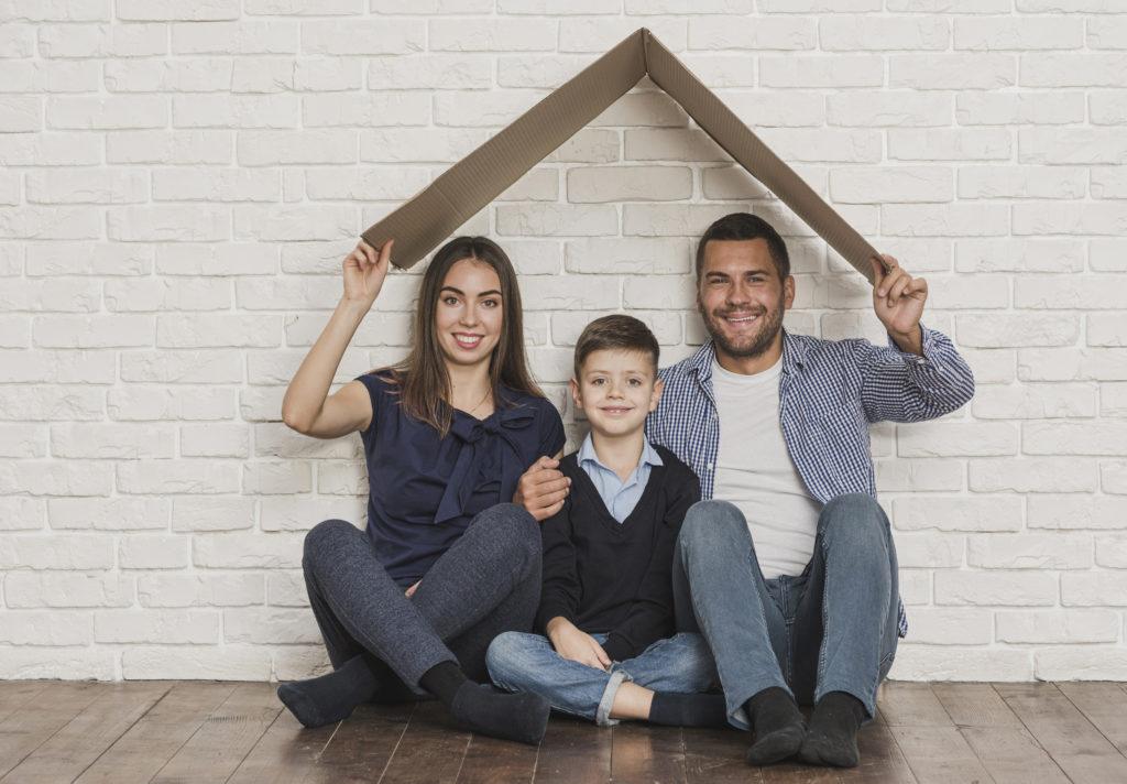 un couple et leur enfant assis sur le plancher de leur maison de montréal devant un mur de briques blanc et tenant au-dessus de leur tête un toit en carton