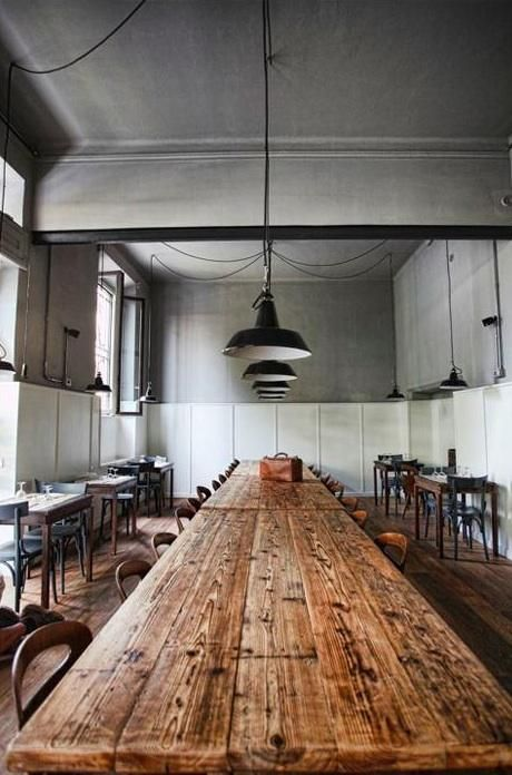 Communal wooden table at the U Barba Osteria restaurant in Milan.